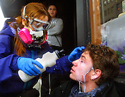 A protester is treated by another with a milky mixture which helps take the sting out of pepper spray. Portland Police sprayed a crowd gathered on the sidewalk at Washington and 3rd, an estimated 40,000 took to the streets of downtown Saturday for an anti-war protest and march.
