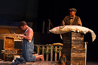 Riley Alward as Huck Finn looks through some of Jim's belongings while Jim played by Angel Douglas guts a catfish during dress rehearsal for Big River with the Streetcar Company at Interlakes High School Auditorium on Tuesday evening.  (Karen Bobotas/for the Laconia Daily Sun)