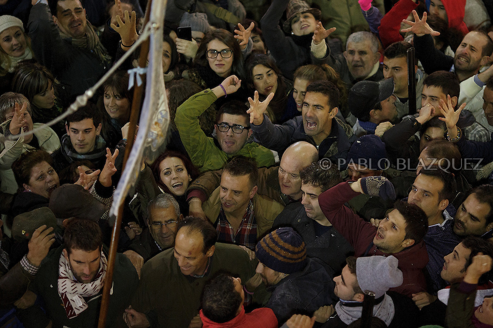 "Revelers cheers as the steward 'Paladin' carrying a banner with the image of Immaculate Conception passes by inside the church during the ""La Encamisa"" Festival on December 7,  2014 in Torrejoncillo, Extremadura region, Spain. ""La Encamisa"" is an ancient festival in honor of Immaculate Conception. Hundreds of horsemen wearing a white sheet gather outside the church in the main square. The procession starts when a banner with the image of Immaculate Conception is delivered to the horse rider steward 'Paladin' and people cheer and shoot blanks. There are bonfires along the way where people gather to chat, eat traditional sweets and drink local wine. The origin of this tradition is unknown but it is believed the festival comes from a military event in which people from Torrejoncillo were involved. The war in Flanders in 1585, the Battle of Pavia or a legend of the siege suffered by city of Coria. (© Pablo Blazquez)"
