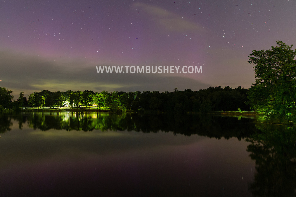 The northern lights are visible above the horizon and reflected in the lake at Fancher-Davidge  in Middletown, New York.  The aurora borealis was visible to observers in lower latitudes because of a severe geomagnetic storm.