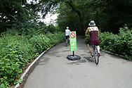 "Biker going past the ""Walk Bikes on Paths"" sign in Central Park"