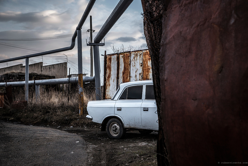 An old Lada is parks below soviet era gas pipes in the city of Gyumri. Armenia