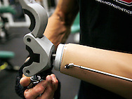 Bob Radocy of TRS Inc. attaches a prosthetic hand designed for weightlifting to his prosthetic arm at a gym in Boulder, Colorado August 21, 2009. Radocy designs and builds prosthetic attachments that allow amputee athletes to participate in multiple sports.  REUTERS/Rick Wilking (UNITED STATES)