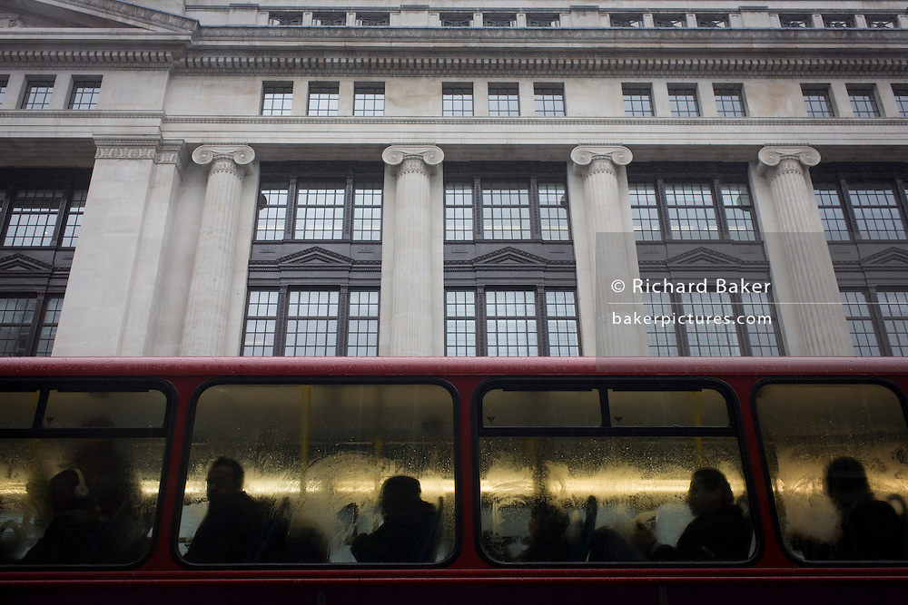 Silhouettes of anonymous bus commuters and a large corporate building during damp, gloomy weather in central London.