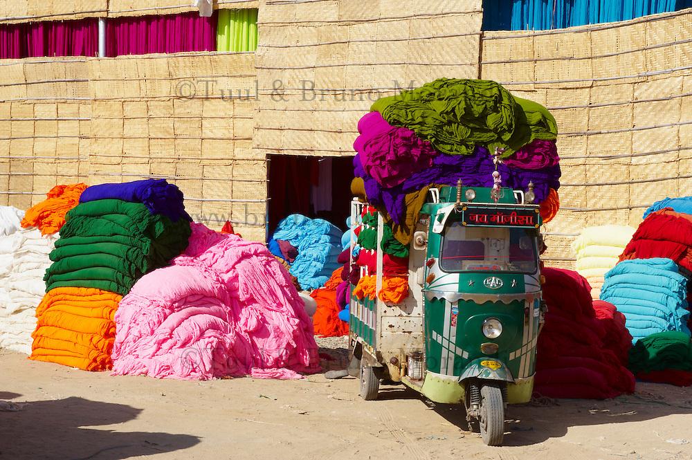 Inde, Rajasthan, Usine de Sari, transport des tissus destines a la fabrication des saris, Les tissus sechent en plein air. Ramassage des tissus secs par des femmes et des enfants avant le repassage. Les tissus pendent sur des barres de bambou. Les rouleaux de tissus mesurent environ 800 m de long. // India, Rajasthan, Sari Factory, transportation of the textile use for sari manufacture, India, Rajasthan, Sari Factory.