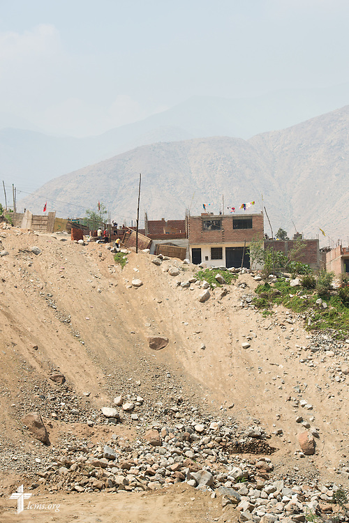 Houses sit on the edge of a hill damaged by landslides near Huayaringa, Peru, on Tuesday, April 7, 2015. LCMS Communications/Erik M. Lunsford