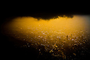 Dark storm clouds loom over Bogota, Colombia at sunset in this aerial view.