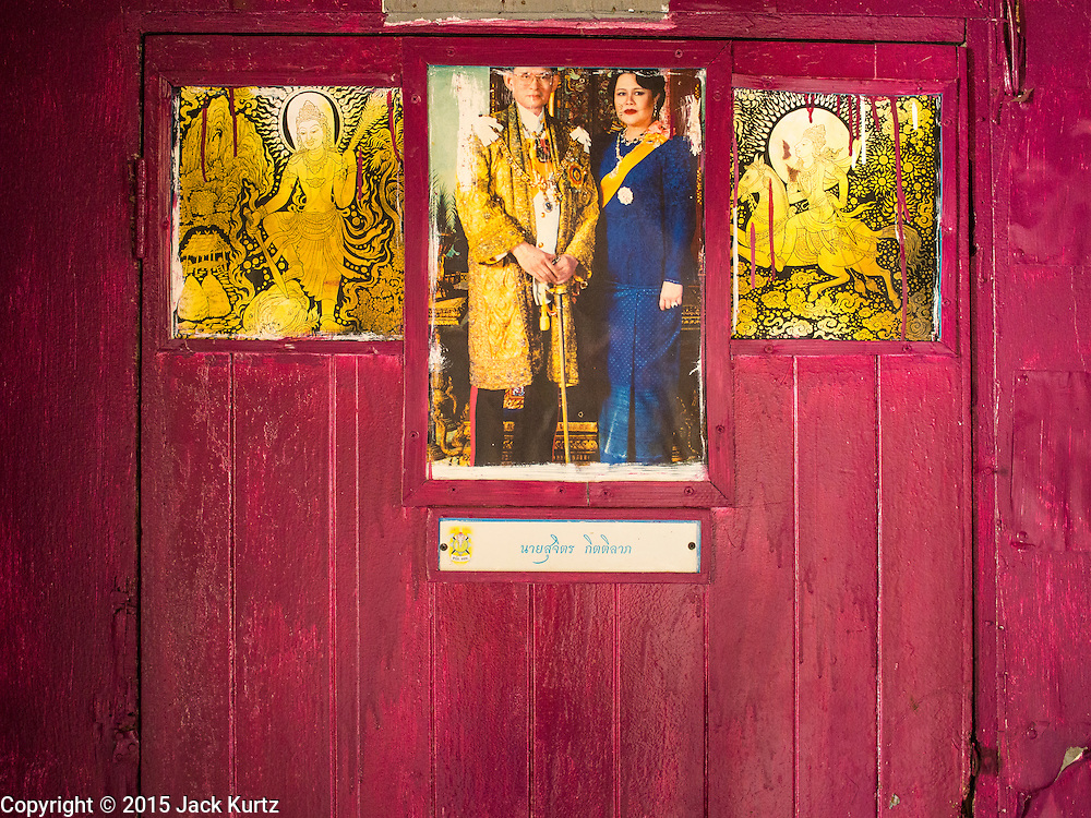 17 MARCH 2015 - BANGKOK, THAILAND: A portrait of Bhumibol Adulyadej, the King of Thailand, and his wife, Queen Sirikit, hanging on an interior doorway in the old Customs House in Bangkok. The old Customs House was once the financial gateway to Thailand (before 1932 called Siam). It was designed by an Italian architect in the 1880s. In the 1950s, customs moved to new, more modern building and the Customs House became the headquarters for the Marine firefighters. The firefighters now live in the decrepit buildings with their families.    PHOTO BY JACK KURTZ
