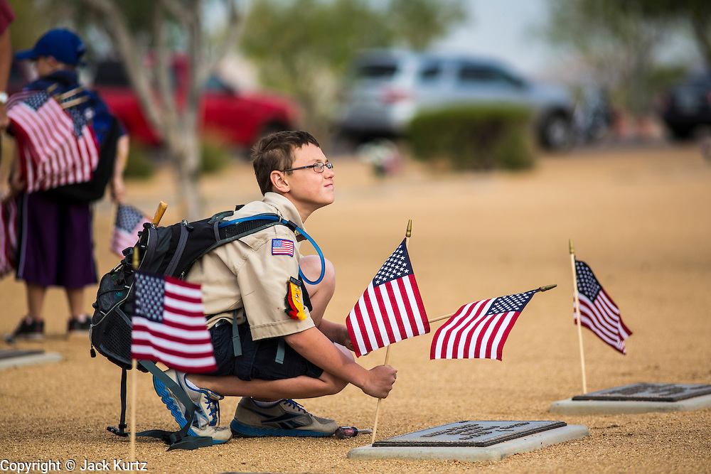 26 MAY 2012 - PHOENIX, AZ: A Boy Scout places an American flag on a veterans' grave at the National Memorial Cemetery in Phoenix, AZ, Saturday. Hundreds of Boy and Girl Scouts along with the Young Marines, a Scout like organization, place American flags on veterans' graves in the National Memorial Cemetery in Phoenix every year on the Saturday before Memorial Day.     PHOTO BY JACK KURTZ