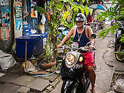 30 JULY 2016 - BANGKOK, THAILAND:  A man navigates his motor scooter through the Pom Makahan Fort slum. The community is known for fireworks, fighting cocks and bird cages. Residents of the slum have been told they must leave the fort and that their community will be torn down. Mahakan Fort was built in 1783 during the reign of Siamese King Rama I. It was one of 14 fortresses designed to protect Bangkok from foreign invaders. Only of two are remaining, the others have been torn down. A community developed in the fort when people started building houses and moving into it during the reign of King Rama V (1868-1910). The land was expropriated by Bangkok city government in 1992, but the people living in the fort refused to move. In 2004 courts ruled against the residents and said the city could take the land. Eviction notices have been posted in the community and people given until April 30 to leave, but most residents have refused to move. Residents think Bangkok city officials will start evictions around August 15, but there has not been any official word from the city.     PHOTO BY JACK KURTZ