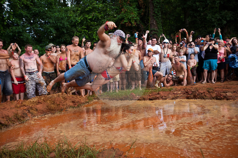 Robert Sprague and his wife Rawni start the Mud pit belly flop contest during the annual Summer Redneck Games Dublin, GA.