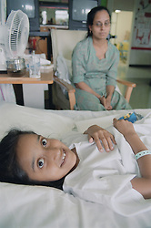 Young girl with spinal disease lying on hospital bed on Spinal ward with mother sitting beside her,