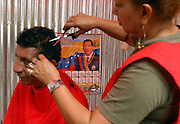 Caracas, Venezuela<br />Near the Plaza Bolivar in central Caracas, a hairdresser demonstrates 'Bolivarian revolutionary solidarity', by giving free haircuts (or a voluntary donation). A poster of Chavez adorns the wall.