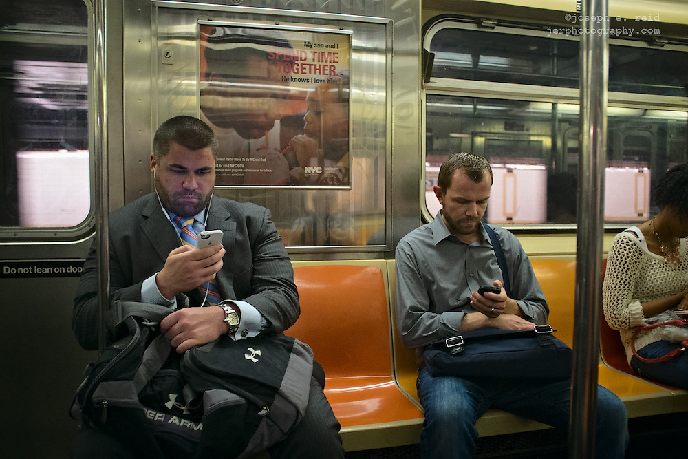 Men with smartphones riding subway