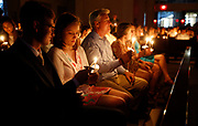 Parishioners light one another's candles as they observe the Easter Vigil during the celebration of Holy Week at St. Francis of Assisi University Parish in Tuscaloosa. [Staff Photo/Gary Cosby Jr.]