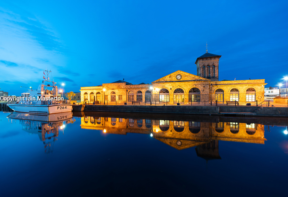 Night view of Illuminated Forth Ports building reflected in dock at night in Leith, Edinburgh, Scotland, UK
