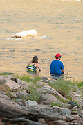 Couple enjoying the water at Johnny Walker camp during sunset on the Middle Fork of the Salmon River, Idaho.