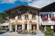 MITTENWALD, GERMANY - SEPTEMBER 01, 2010: Unidentified people relax at the small street cafe with traditional Bavarian painted house at the background in Mittenwald, Germany.