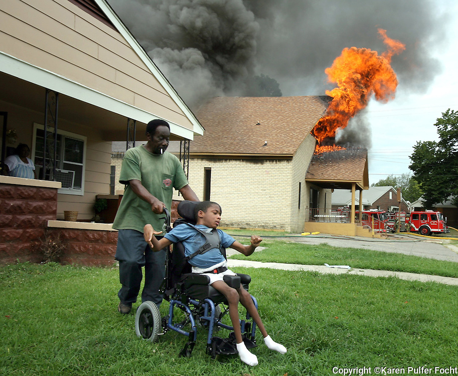 June 29, 2010 - Relatives bring a handicapped child to safety during a fire Tuesday morning. Eddie Grays pushes Kahlil Bringham,14, away from his home as the fire raged next door to their house.  Memphis Firefighters  fought a fire at Light of Glory International Church located at 714 North 7th.
