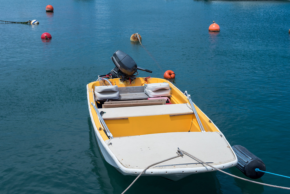 A small motoroboat is tied to a pier in a harbor.