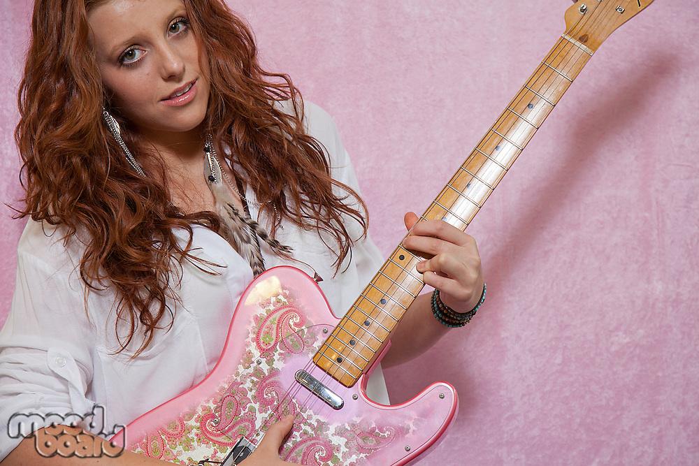 Pretty teenage girl playing guitar