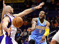 Nov. 12, 2012; Phoenix, AZ, USA; Denver Nuggets guard Andre Iguoldala (9) makes a pass against the Phoenix Suns center Marcin Gortat (4) during the first half at US Airways Center. Mandatory Credit: Jennifer Stewart-US PRESSWIRE..