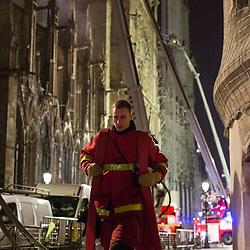 Pompiers de Paris et forces de l'ordre de nuit sur l'île de la Cité à proximité de l'incendie qui a embrasé la cathédrale Notre Dame le lundi 15 avril 2019. Relai, ravitaillement et repos des équipes de sapeurs pompier. Remise en condition et rangement des lances incendies et intervention sur la nef au moyen de Bras Elévateurs Articulés. Badauds parisiens sur les bords de Seine observant l'embrasement.<br /> Avril 2019 / Paris (75) / FRANCE<br /> Voir le reportage complet (77 photos) https://sandrachenugodefroy.photoshelter.com/gallery/2019-04-Incendie-de-Notre-Dame-de-Paris-Complet/G0000RK6tU54nz3I/C0000yuz5WpdBLSQ
