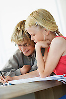 Brother and Sister Doing Homework at table in home
