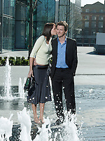 Mid-adult couple standing between water jets of fountain woman kissing man