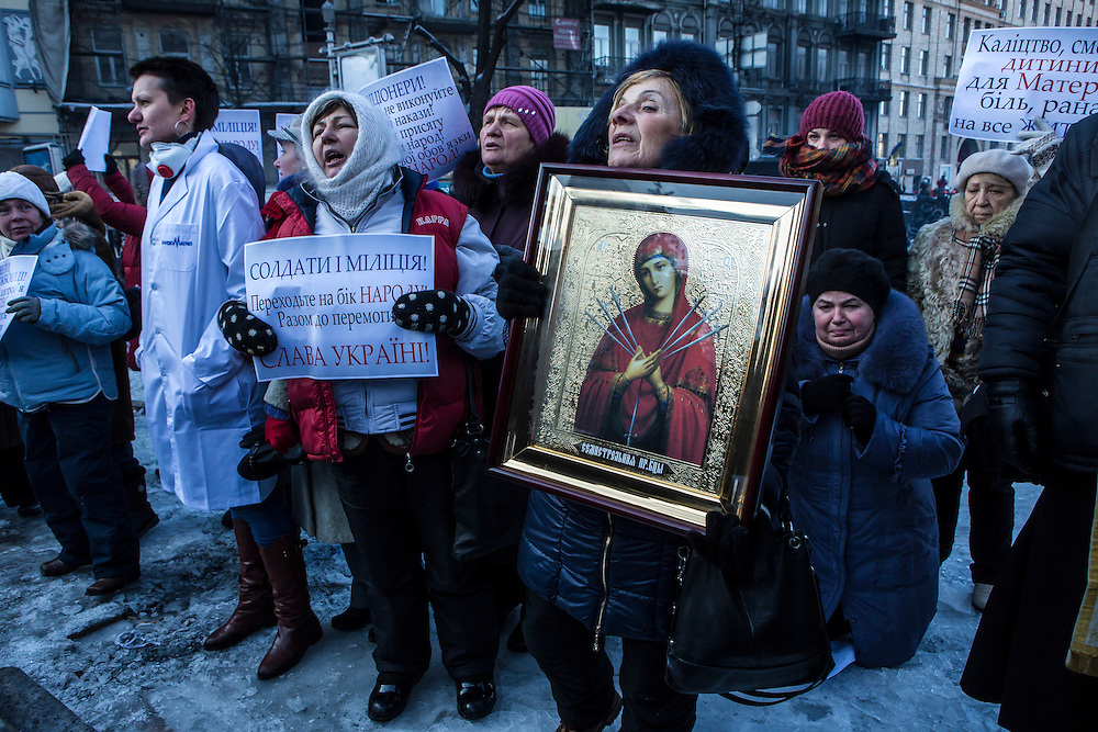 KIEV, UKRAINE - JANUARY 24: A group of Ukrainian Orthodox women pray in front of a line of police officers near the Cabinet of Ministers building on January 24, 2014 in Kiev, Ukraine. After two months of primarily peaceful anti-government protests in the city center, new laws meant to end the protest movement have sparked violent clashes in recent days. (Photo by Brendan Hoffman/Getty Images) *** Local Caption ***