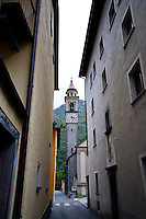 Ticino, Southern Switzerland. Moghegno.  Church tower seen through a narrow street.