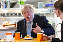 © Licensed to London News Pictures. 14/05/2015. LONDON, UK. The Mayor of London, Boris Johnson eating a bacon roll whilst meeting volunteers and staff at social supermarket the Community Shop in Gipsy Hill, south London on Thursday, 14 May 2015 to announce plans to pilot similar schemes across the capital to allow members of the public buy food reduced by up to 70 per cent of normal retail prices by selling surplus products that larger retailers can't use. Photo credit : Tolga Akmen/LNP