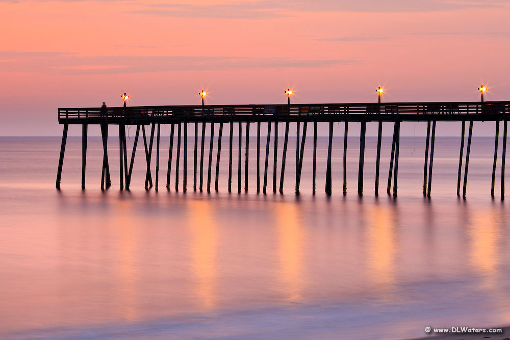 A long exposure smooths out the waves in this  picture of the Outer Banks, Kitty Hawk pier at sunrise.