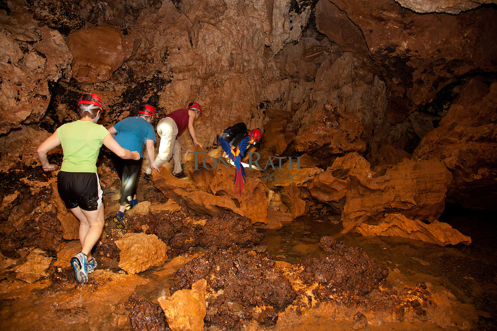 Medium shot shows tourists climbing over rocks in the Actun Tunichil Muknal Cave Natural Monument in the Tapir Mountain Nature Reserve, Teakettle Village, Cayo District, Belize.
