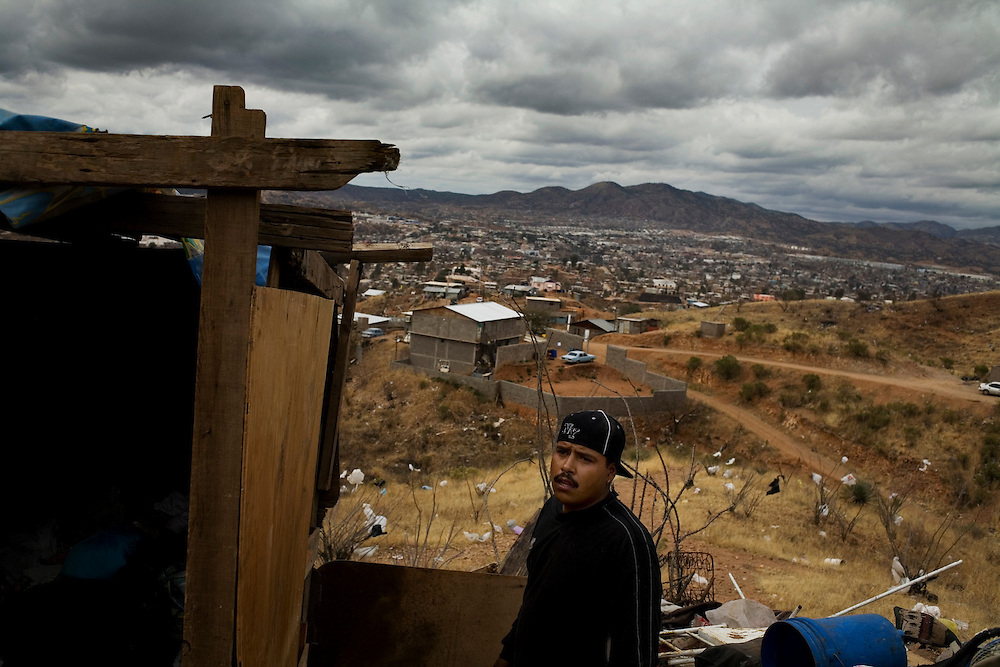 A man puts together a shack made of plywood in the hills of Nogales. He and his family have been sleeping outside since their tin and cardboard shack burned to the ground two weeks before. Even before the accident the family had no water or electricity and their only source of income was selling scavenged trash.