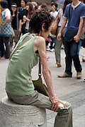 female person with anorexia symptoms resting in public pedestrian area