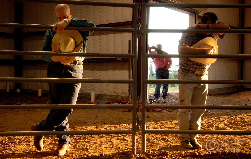 Three cowboys bow their heads in prayer during the Christian rodeo held each Thursday by the Cowboy Church in Amarillo, TX in their own arena behind the church, Thursday July 14, 2005. The church rodeo, in which semi-professional bull riders compete, is designed to bring in people who are interested in the sport then expose them to the teachings of Jesus.