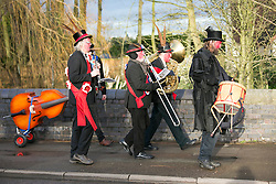 """© Licensed to London News Pictures.10/1/2015.Sharnford, Leicestershire, UK. The annual plough tour by the Hinckley Bullockers took place today. Pictured, walking along the Leicester road in Sharnford. Visiting seven venues around Leicestershire the Bullockers, some with with red painted faces, are seen pulling their decorated plough along the street before stopping to perform traditional dances.<br /> <br /> HISTORY -  On the first Monday after Twelfth Night - Plough Monday - the plough was prepared for the new season, dressed in gaudy ribbons and taken in procession around the villages. In South West Leicestershire the men pulling the plough, who """"raddled"""" their faces, were known as Plough Bullocks and were aided and abetted by dancers who danced dances peculiar to the Eastern Counties. The Plough Bullocks and the Molly Dancers were last seen in this area at the turn of the century in Sapcote.<br />  Traditionally, the Plough Bullockers would stop at public houses, farms and large houses, dance and/or sing and demand recognition in the form of cash donations or drink. If neither was forthcoming the offending landlord's drive was ploughed up. Photo credit : Dave Warren/LNP"""