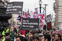 © Licensed to London News Pictures. 19/03/2016. London, UK.  Demonstrators calling for safe passage for refugees walk past a Britain First counter-demonstration in Piccadilly Circus. Thousands march through central London on UN anti-racism day to demand that the British government accept a greater share of refugees seeking asylum in Europe. Photo credit : Rob Pinney/LNP