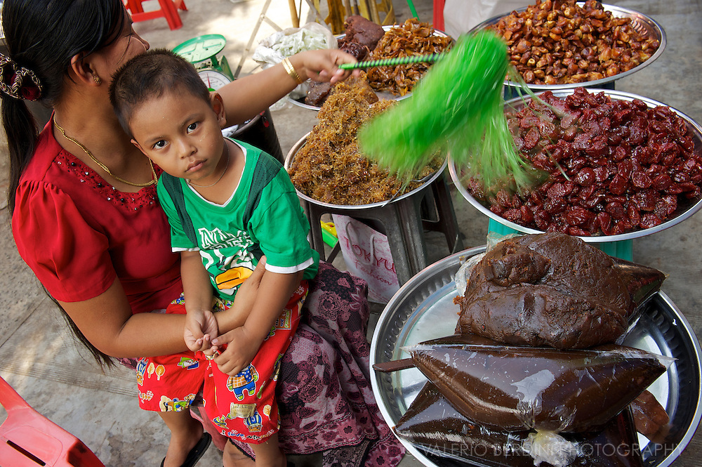 A mother holds her son and brushes away the flies from her collection of Burmese street food.