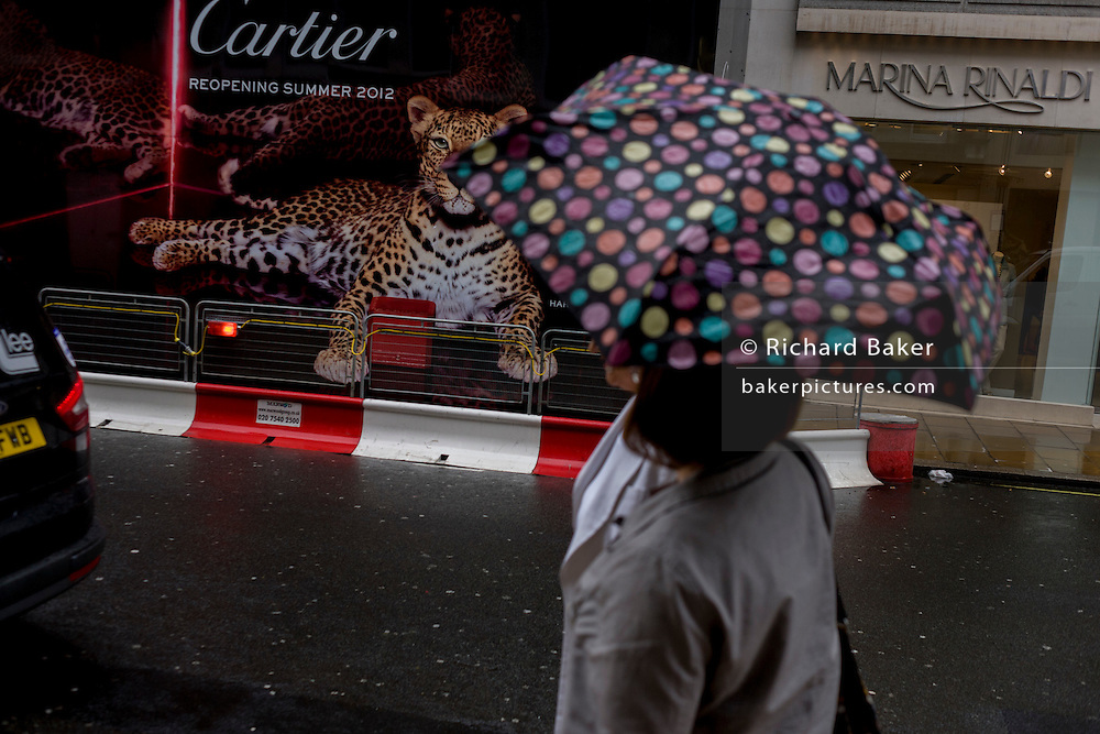 Friends sheltering from April rains under a spotted umbrella walk past a hoarding featuring a leopard for a new Cartier shop