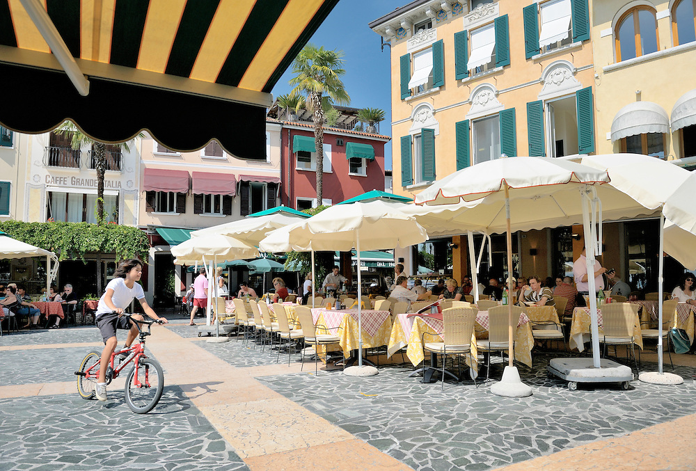 The holiday resort town of Sirmione on Lake Garda, Lombardy, Italy. Street cafes on the Piazza Giosue Carducci. Lago di Garda.
