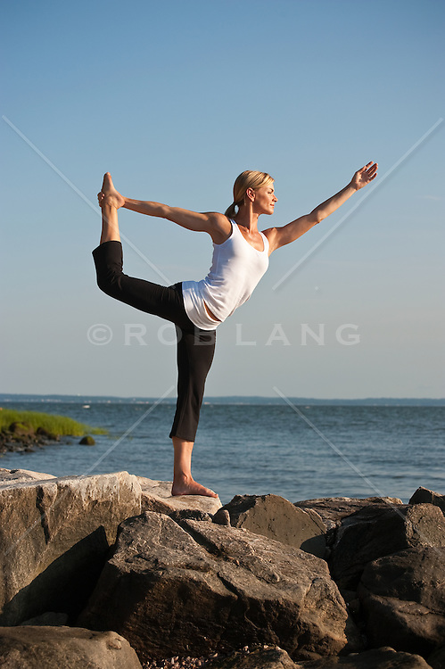 Woman doing yoga on rocks by the ocean