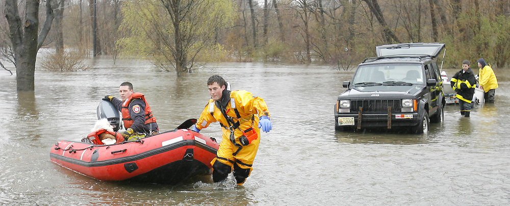 Firefighters evacuate an elderly woman from a flooded housing development in New Milford, New Jersey on Monday 16 April 2007. A large storm delivered records amount of rain to the East Coast of the United States over the weekend and today, causing New Jersey to declare a state of emergency.