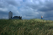 A man stands on his own on a grassy bank to cut a lonely figure in long grass on an embankment near the tall Canary Wharf tower structure a mile away in the background at Dockland's area of East London. Above the grassy bank at Mudchute, a city farm on London's Isle of Dogs, England, the sky is threatening with gathering clouds but lights still picks out the man against the darkening skyline. He stands with arms folded looking thoughtfully at the ground as if depressed or considering his isolation in the world. It is a seemingly rural location but is, in fact, an area of inner-city London, close to major construction projects, transforming Docklands into a major centre for finance and new housing.