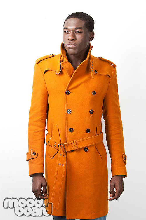 Young African American man in orange trench coat standing against white background