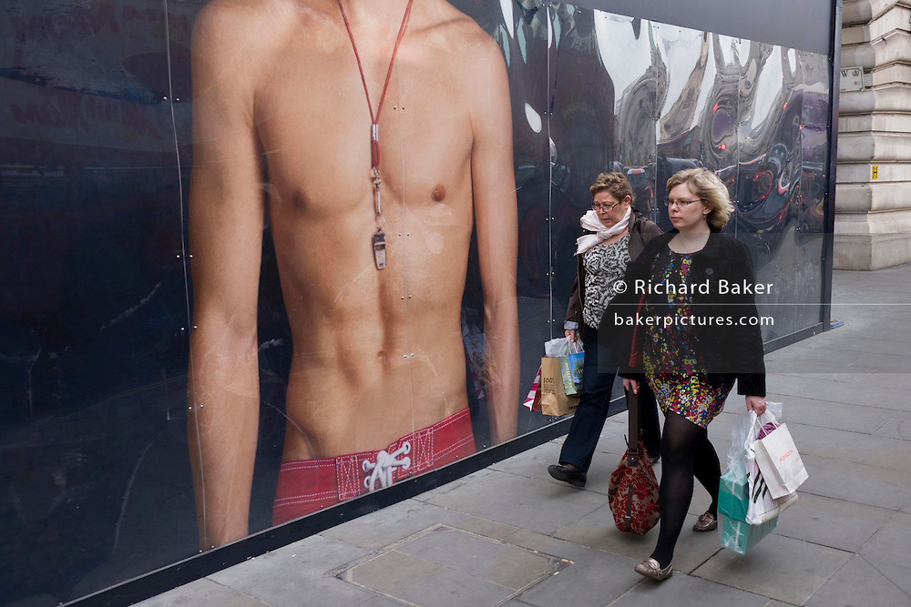 Two women walk past a giant ad mural of a bare-chested young male model