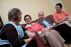 Carer talking older couple and their daughter at home,