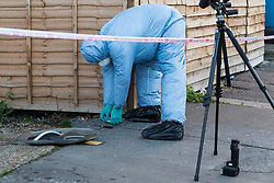 A forensics investigator places a measurement scale next to a bloodstained knife on Brookdale Road, an adjacent side street, following a stabbing at a Costa Cafe On Bowes Road, Arnos Grove  in which a male victim has been left in critical condition. Arnos Grove, North London, November 12 2018.