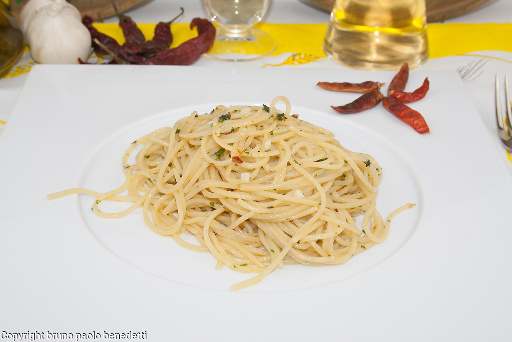 garlic hot pepper spaghetti side view close-up on white dish with hot pepper garnish and white wine glass and bottle, garlic and extra virgin olive oil on blured background, traditional italian food
